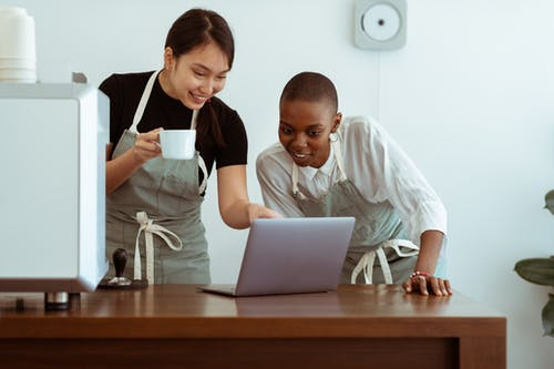 Cheerful coworkers using laptop and chatting in kitchen
