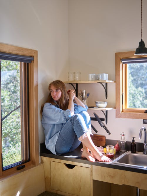 Sad woman sitting on kitchen counter and looking away