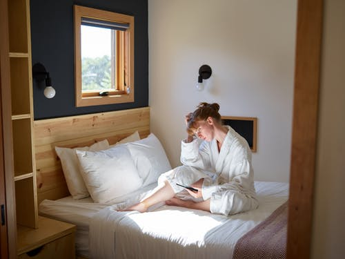 Thoughtful woman reading book using e reader on bed