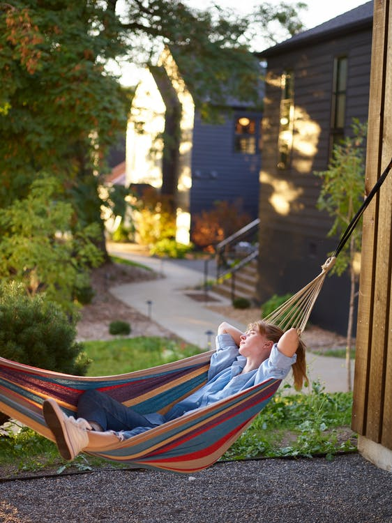 Relaxed woman chilling in hammock in countryside