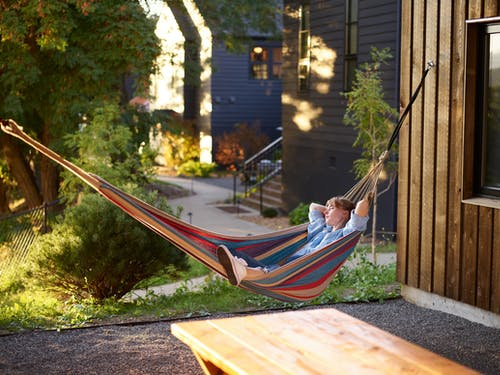 Full body relaxed female in casual wear resting on striped hammock with hands behind head on sunny evening in countryside area