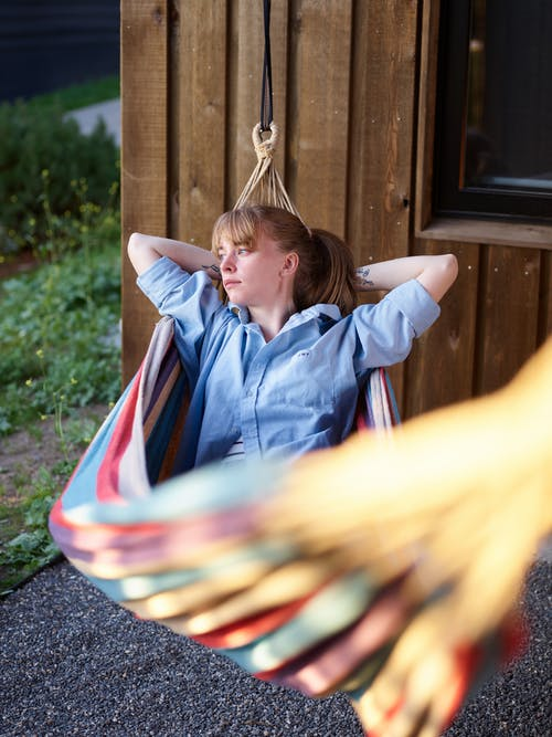 Pensive woman in blue blouse resting in hammock