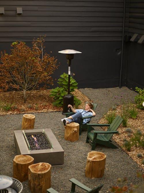 Relaxed woman on garden chair near fireplace