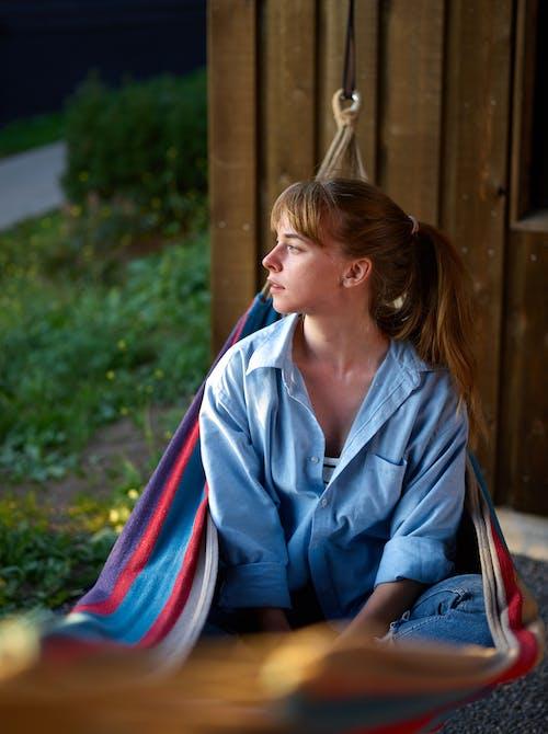 Positive woman sitting in hammock