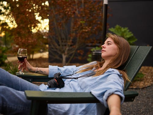 Calm woman with glass of red wine on deckchair