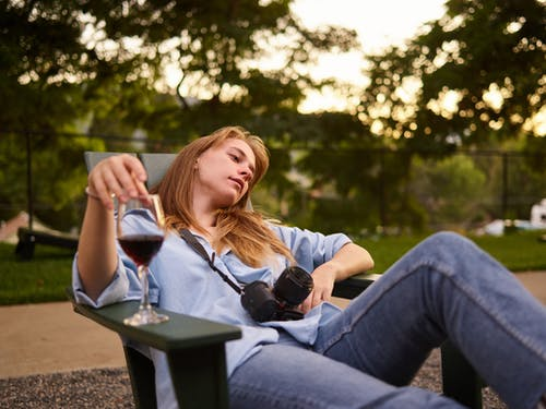 Unhappy woman with glass of wine resting on garden chair