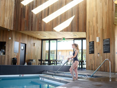 Woman in swimsuit standing near indoor swimming pool
