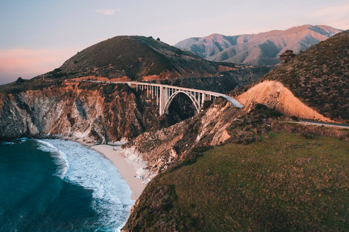 Suspension bridge in mountainous valley near turquoise ocean during sundown