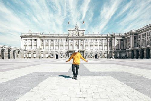 Faceless tourist with outstretched arms standing alone on square near historical palace