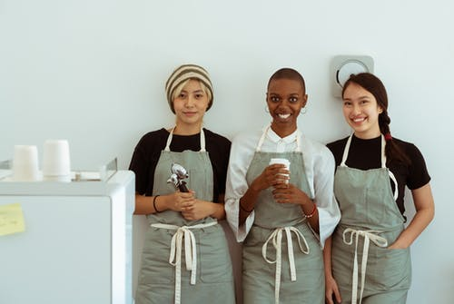Delighted baristas with portafilter and paper cup