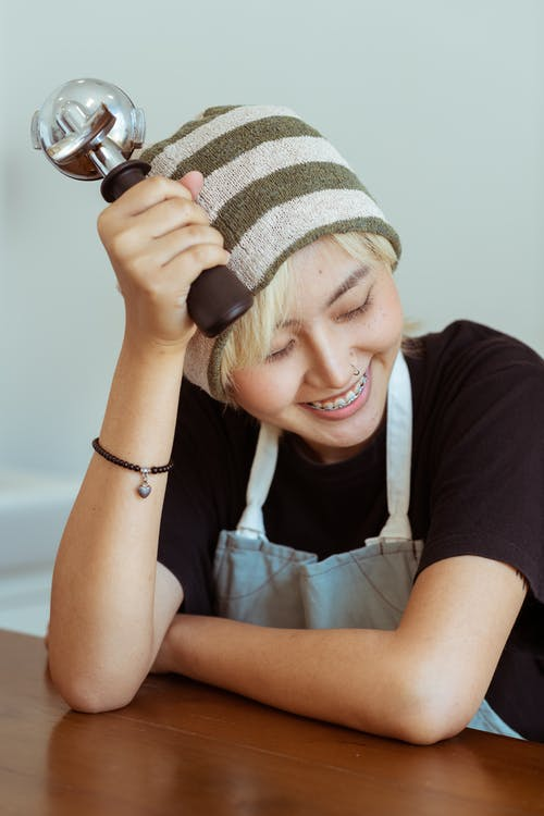 Happy smiling Asian female barista wearing apron and striped hat sitting at table at leaning on hand with portafilter