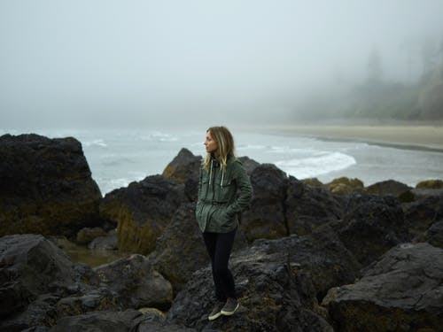 Calm woman standing on rocky coast on foggy day
