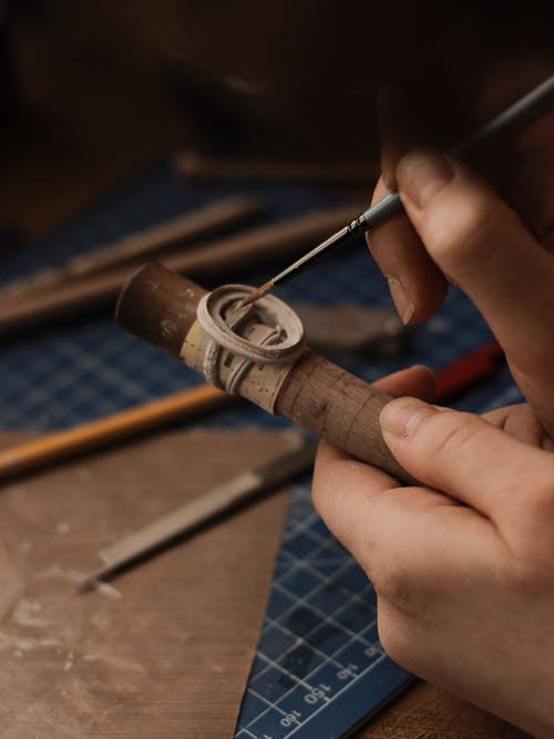 Person Holding Brown and Silver Smoking Pipe