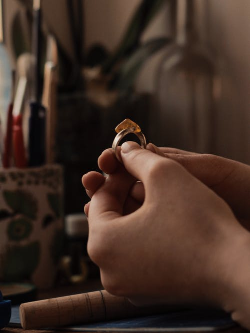 Person Holding Gold and Silver Ring