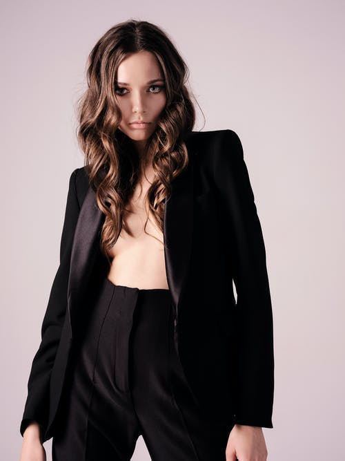 Stylish confident young woman in suit on naked body