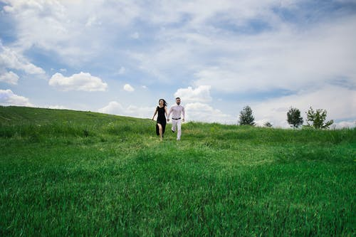 Anonymous young man and woman in classy clothes holding hands and running on green grassy meadow against cloudy blue sky