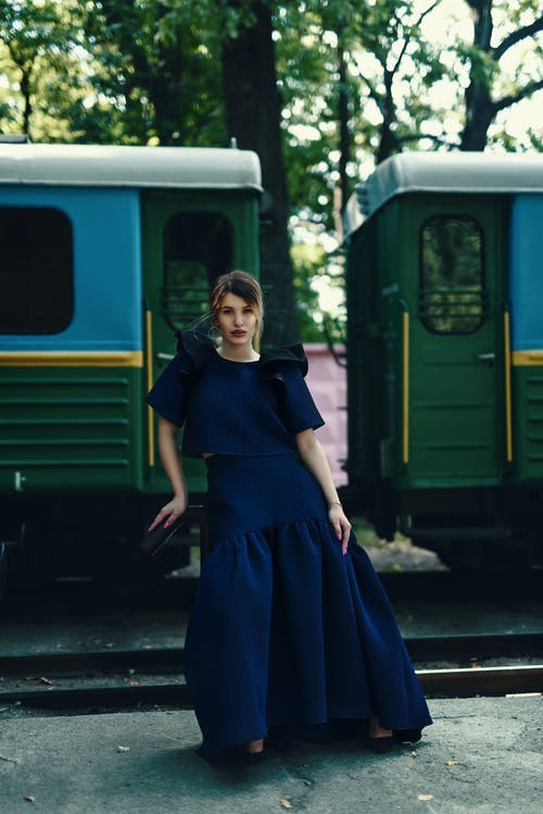 Full length of young elegant female traveler in maxi dress sitting on suitcase and looking at camera near retro train on railway platform