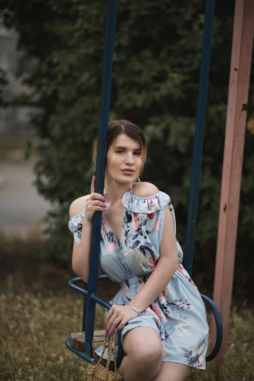 Romantic young female in stylish dress sitting on swing in park and looking at camera