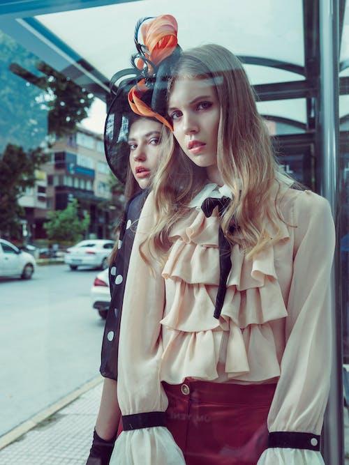 거리에 서있는 창조적 인 모자에 유행 젊은 여성