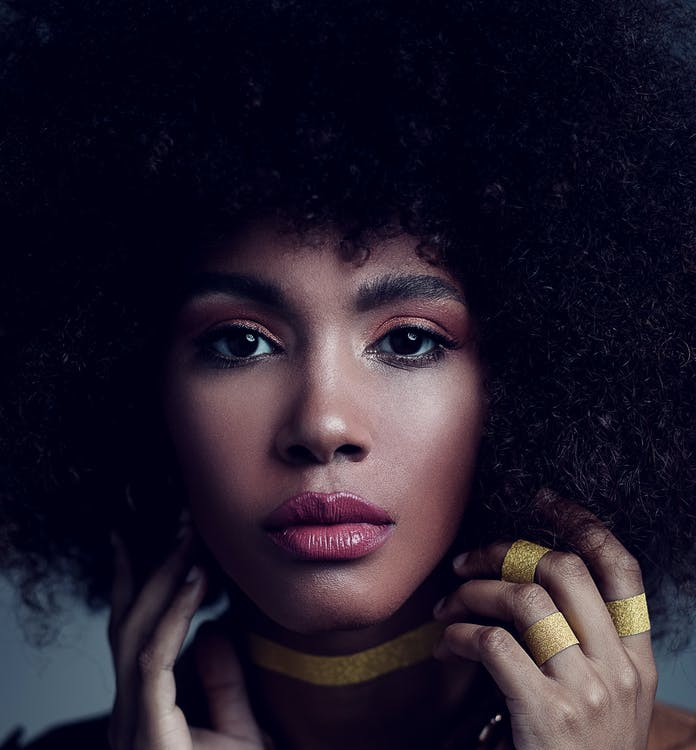 Young pensive African American female model touching curly hair and looking at camera