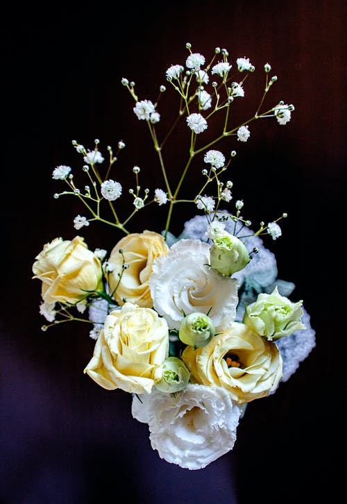 From above of elegant bouquet of fresh yellow roses arranged with white lisianthus and common gypsophila flowers