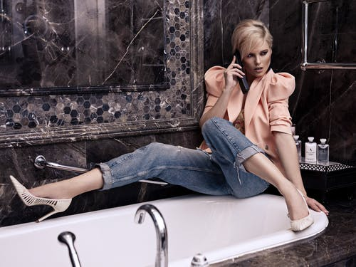 Stylish young female with short blond hair in jeans and high heels having phone conversation sitting near bathtub