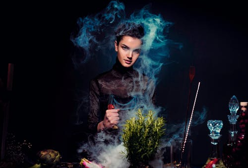 Graceful young female alchemist with knife in hand in black outfit preparing potion from various herbs among smoke in dark room