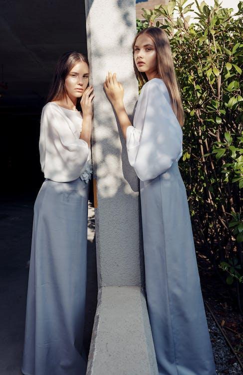 2 Women in Long Sleeve Dress Standing Outside