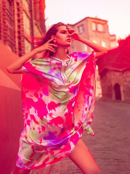 Fashionable young woman in colorful outfit on street