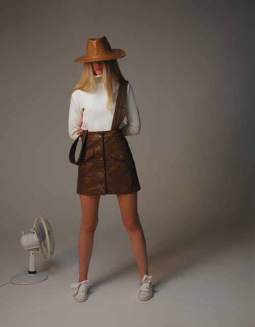 Full length faceless stylish female with blond hair wearing white turtleneck and leather skirt standing in studio near white wall with fan