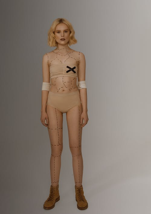 Full body young female with short hair wearing lingerie and boots with dotted lines on the body for plastic surgery