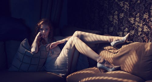 Young female in short dress and shoes touching face while lying on comfortable couch with cushions in dimly illuminated living room
