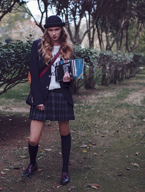 Trendy young woman with books in park
