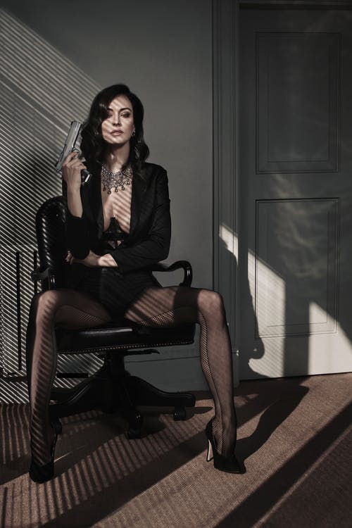 Full body of stylish provocative female wearing black jacket on underwear sitting on chair with pistol
