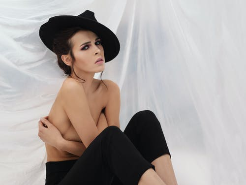 Young sensual female covering naked breast while sitting in stylish hat and pants against white fabric