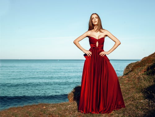 Woman in Red Dress Standing on Cliff