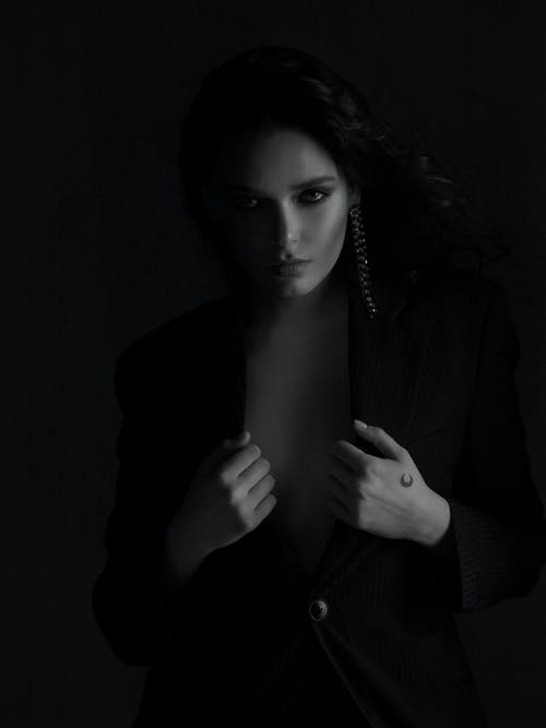 Black and white of elegant woman with makeup in black jacket showing bare breast