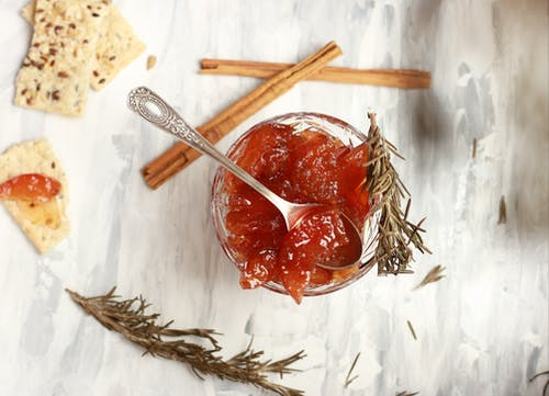Top view composition of bowl with delicious jam in cup with rosemary sprigs and crispbread with cinnamon sticks