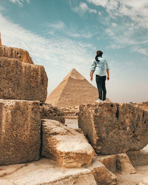 Traveler standing on stone monument in desert