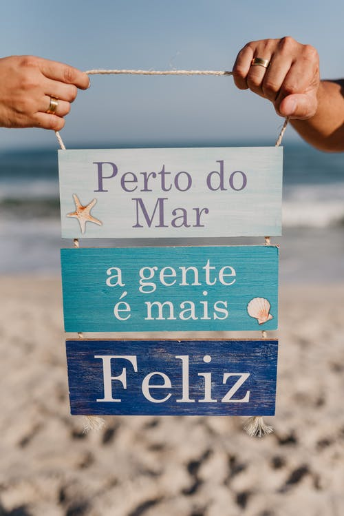 Crop hands of faceless persons holding wooden sign with inscription on Spanish on sandy beach