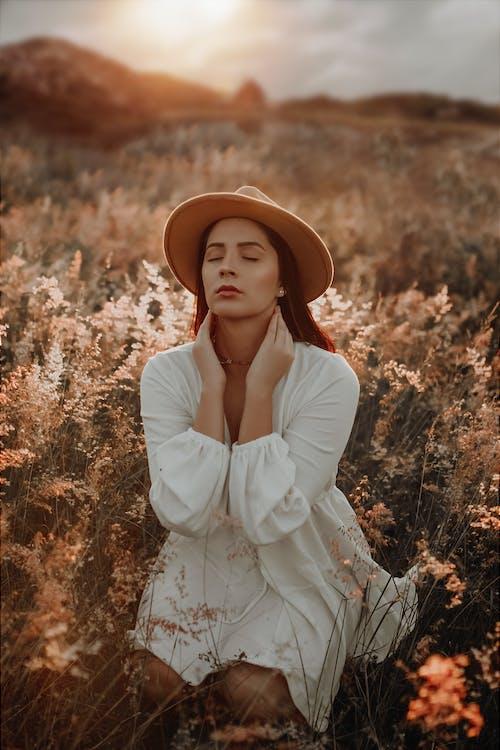 Женщина в белом платье с длинным рукавом в коричневой шляпе стоит на поле коричневой травы