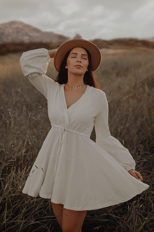 Женщина в белом платье в коричневой шляпе стоит на поле зеленой травы