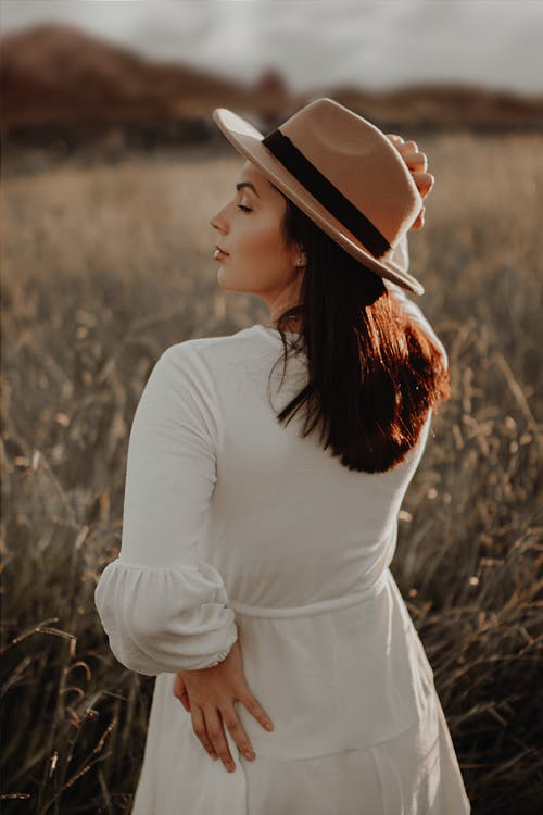 Woman in White Long Sleeve Shirt and Brown Hat Standing on Brown Grass Field