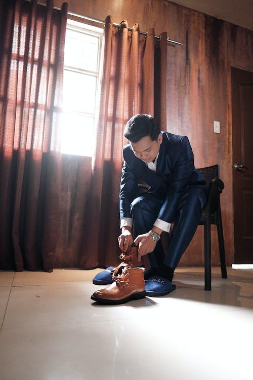 Man in elegant suit putting boots