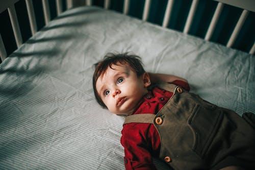 Cute baby boy lying in bed