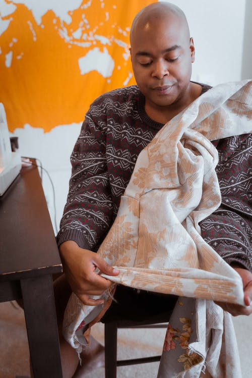 Positive African American male sewer wearing cozy sweater sitting at table and showing stitches on garment while working in contemporary dressmaking studio