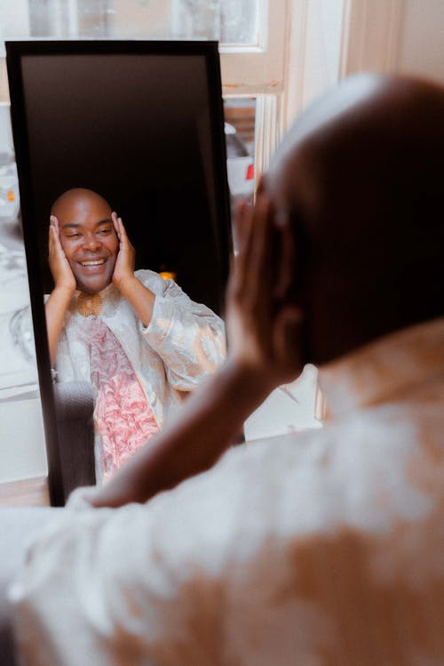 Charismatic bald black man looking in mirror and touching face