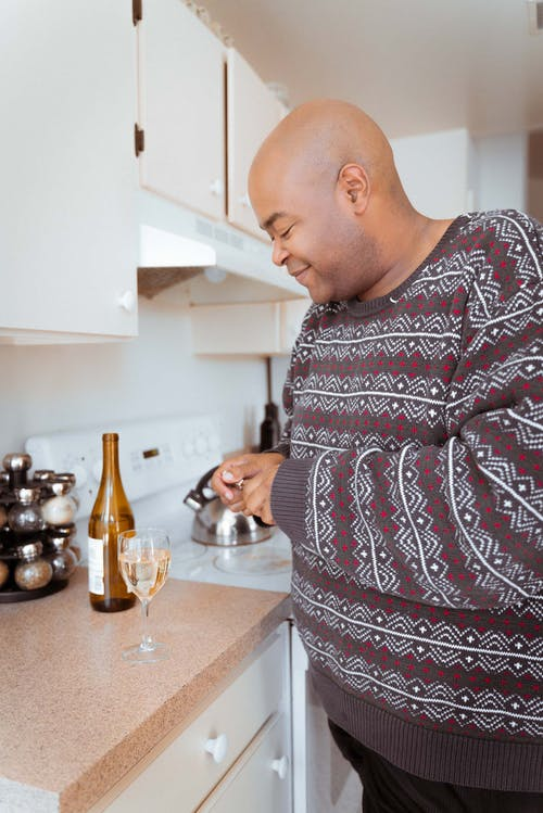 Smiling plus size African American male in cozy sweater standing in kitchen near counter with glass of aromatic white wine