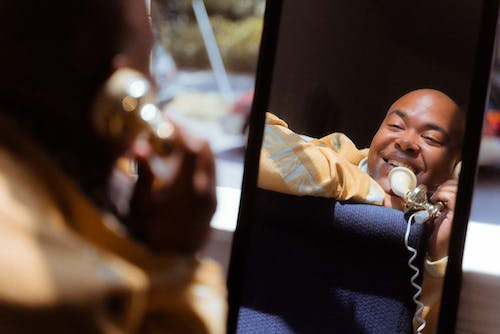 Cheerful black man talking on old fashioned telephone against mirror