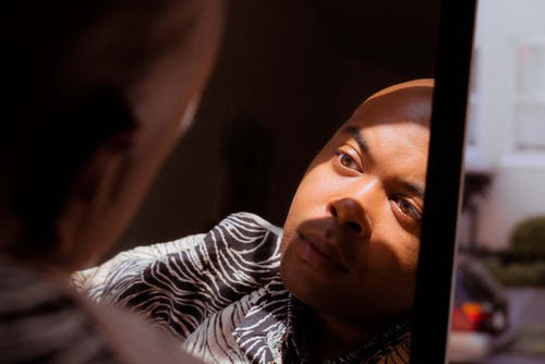 Back view of crop bald wistful ethnic guy with shiny skin looking in mirror in apartment